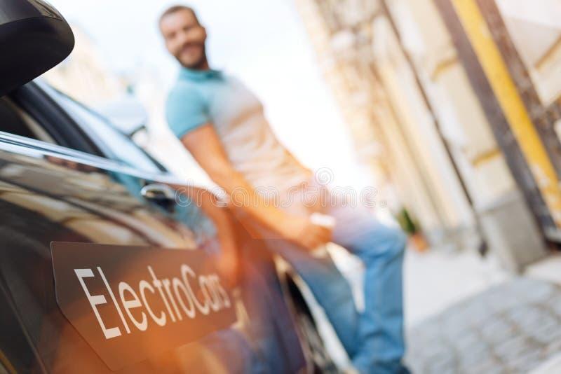 Молодой человек стоя около его нового электрического автомобиля стоковые изображения rf