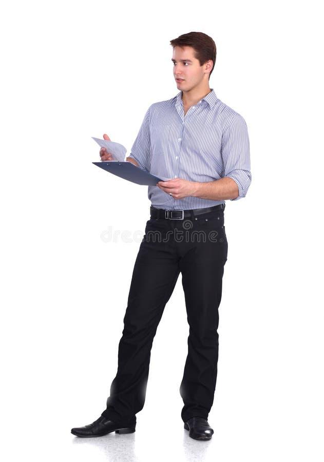 Молодой человек стоя при папка, изолированная на белизне стоковая фотография rf