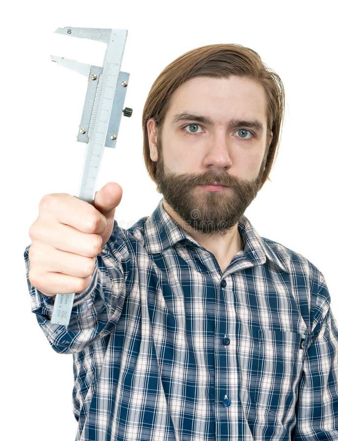 Молодой человек с бородой держа крумциркуль в руке стоковое изображение rf