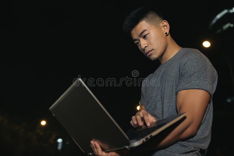 Молодой человек с компьтер-книжкой в городе стоковые изображения rf