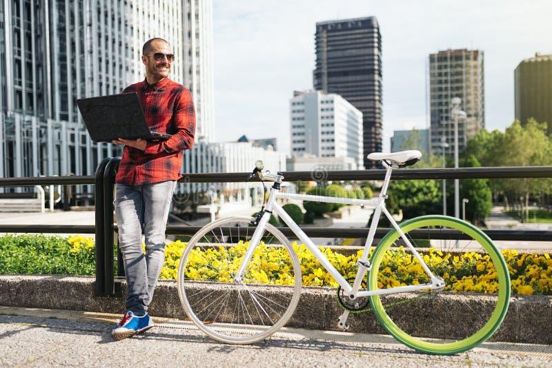 Молодой человек с компьтер-книжкой и фиксированная шестерня bicycle в городе стоковые фото