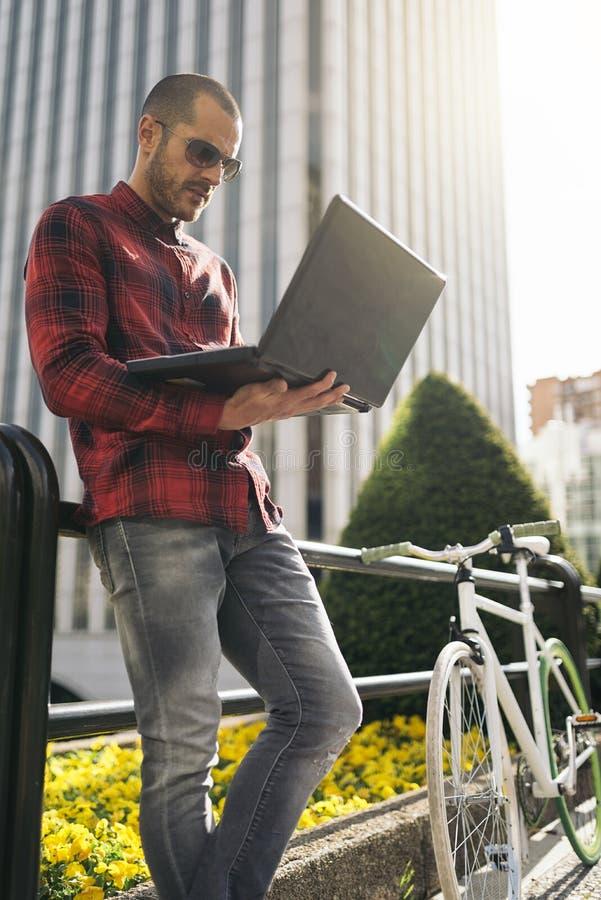 Молодой человек с компьтер-книжкой и фиксированная шестерня bicycle в городе стоковые фотографии rf