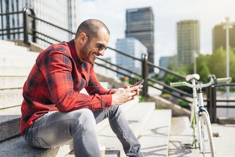 Молодой человек с мобильным телефоном и фиксированная шестерня bicycle стоковая фотография