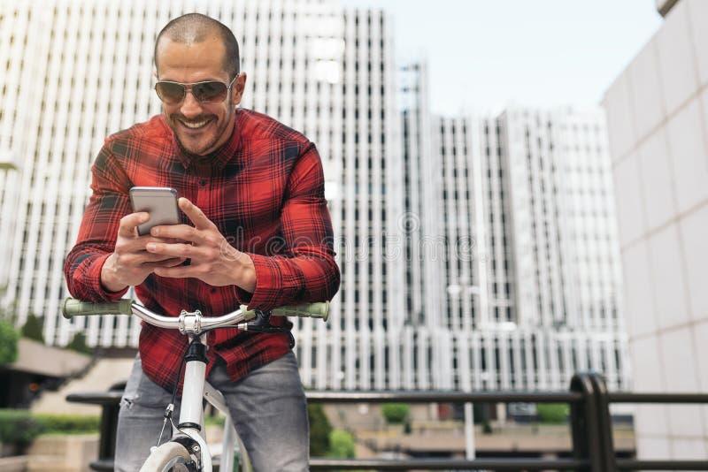 Молодой человек с мобильным телефоном и фиксированная шестерня bicycle стоковые изображения