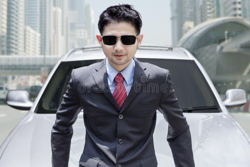 Молодой человек с новым автомобилем на дороге стоковое изображение