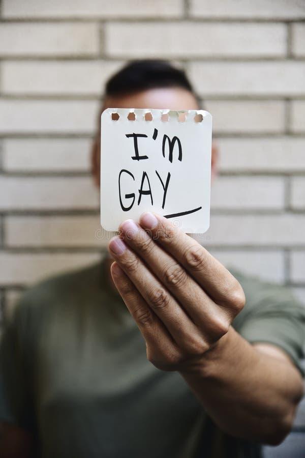 Молодой человек с примечанием с текстом я гомосексуалист стоковая фотография rf