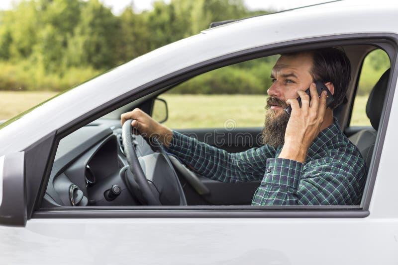 Молодой человек с рукой на рулевом колесе используя мобильный телефон стоковое изображение rf