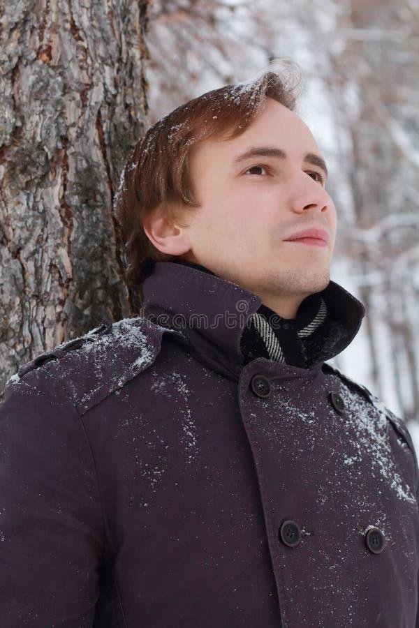 Молодой человек с снежинками в волосах стоит близко дерево стоковые фото