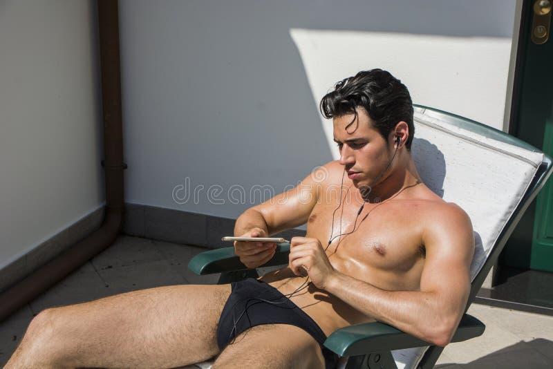 Молодой человек слушая к музыке на кресле для отдыха стоковое фото