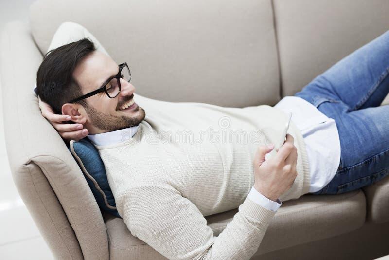 Молодой человек усмехаясь и используя телефон стоковые изображения rf