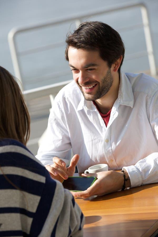 Молодой человек усмехаясь и показывая мобильный телефон женщины стоковые изображения
