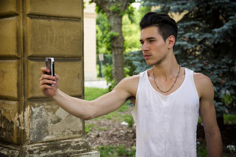 Молодой человек усмехаясь и принимая фото с сотовым телефоном стоковое фото rf