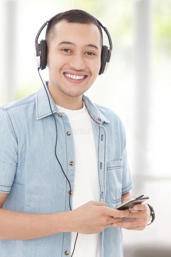 Молодой человек усмехаясь пока слушая музыка на мобильном телефоне с головой стоковая фотография rf