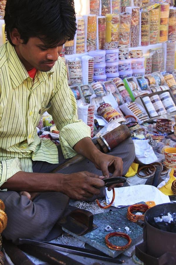 Молодой человек фиксируя красочные браслеты на рынке, Bundi, Rajast стоковые фото