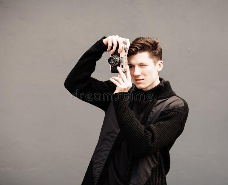 Молодой человек фотографирует модельный винтажную камеру на стене стоковые изображения