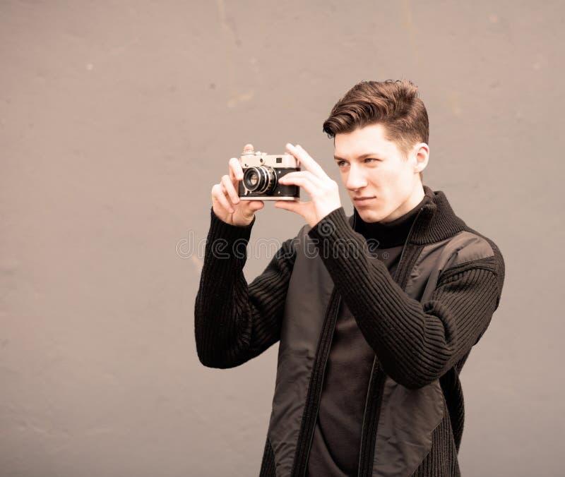 Молодой человек фотографирует модельный винтажную камеру на стене стоковое фото rf