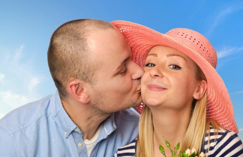 Молодой человек целуя привлекательную женщину стоковые изображения