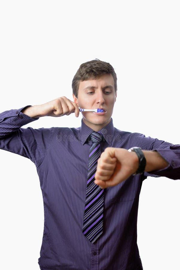 Молодой человек чистя его зубы щеткой также смотрит дальше на вахте на белой предпосылке стоковая фотография rf
