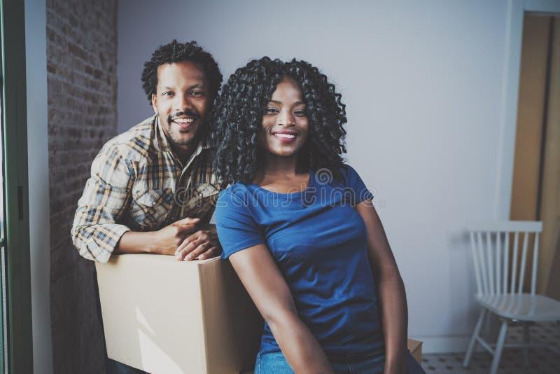 Молодой человек чёрного африканца и его коробки подруги moving в новый дом совместно и делающ красивую жизнь жизнерадостно стоковая фотография rf