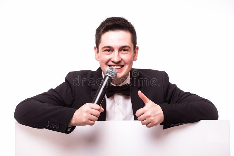 Молодой элегантный говоря человек держа микрофон говоря на таблице с руками подписывает стоковое фото