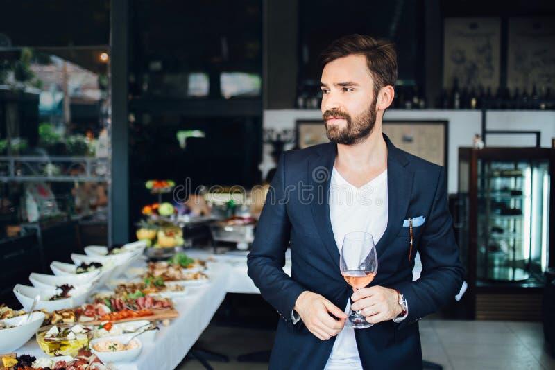 Молодой элегантный человек стоя в ресторане, держа бокал вина укомплектуйте личным составом костюм типа галстука красной s stripe стоковые изображения