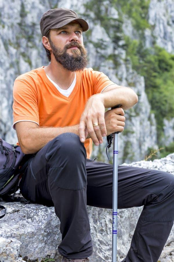 Молодой hiker отдыхая на верхней части горы стоковое изображение