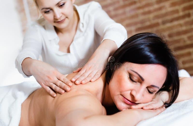 Молодой masseuse делает расслабляющую зону плеча массажа к взрослому wom стоковые фото