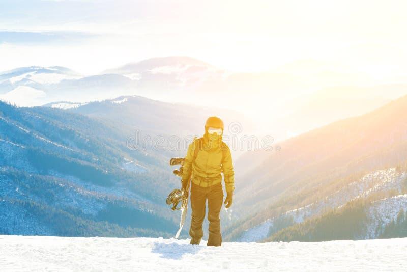 Молодой snowboarder взбираясь вверх гора с его доской в руке на золотом часе стоковая фотография