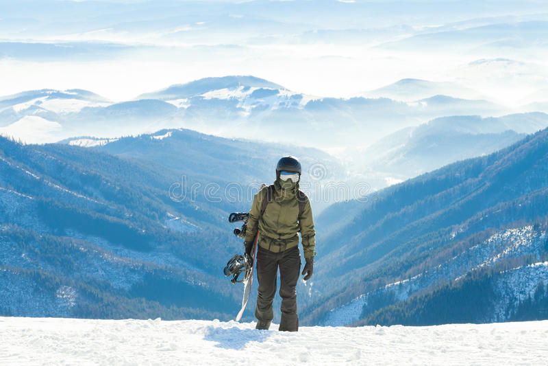 Молодой snowboarder взбираясь вверх гора с его доской в руке стоковое изображение