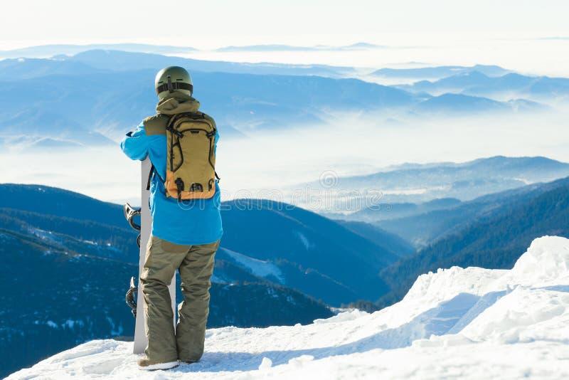 Молодой snowboarder взглянуть на ландшафте от очень верхней части горы стоковые изображения rf