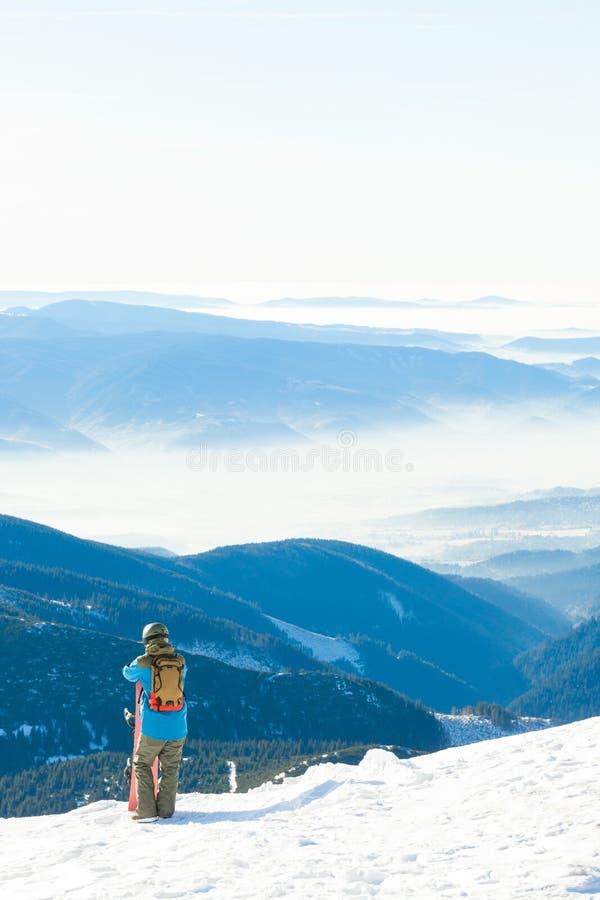 Молодой snowboarder в шлеме взглянуть на ландшафте от очень верхней части горы стоковые изображения rf
