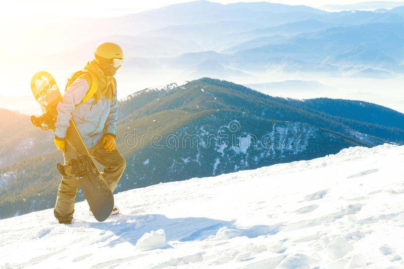 Молодой snowboarder в шлеме идя вверху гора на заходе солнца стоковые фото