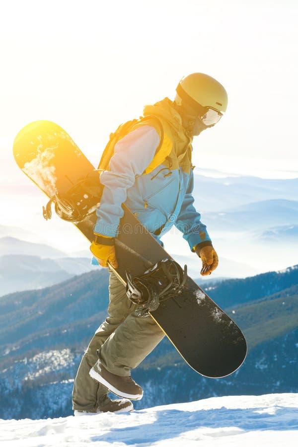 Молодой snowboarder идя вверху гора с солнцем за им стоковые изображения