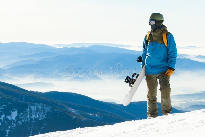 Молодой snowboarder смотря ландшафт от вершины горы стоковое изображение rf