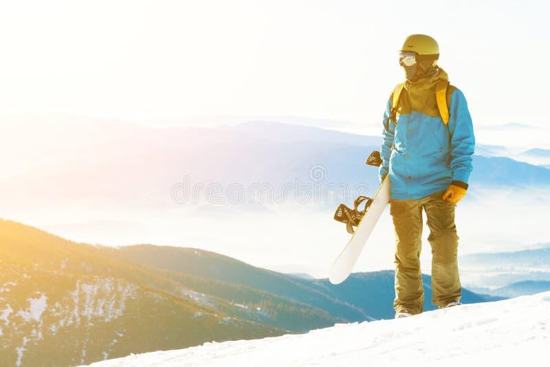 Молодой snowboarder с солнцем за им смотря ландшафт от вершины горы стоковые фото