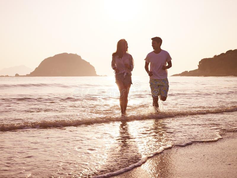 Молодые азиатские пары бежать на пляже стоковое фото