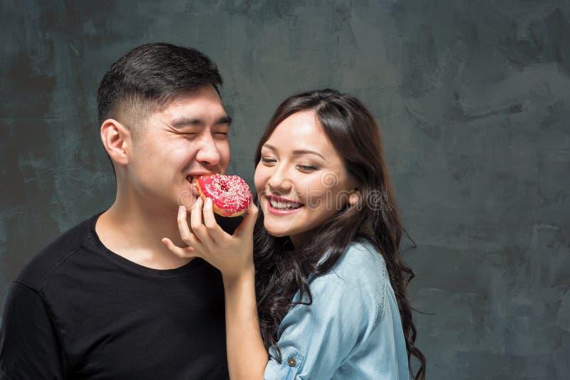 Молодые азиатские пары наслаждаются едой сладостного красочного донута стоковая фотография