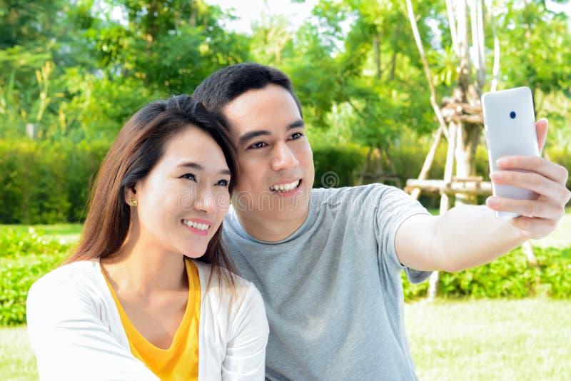 Молодые азиатские пары принимая selfie с умным телефоном стоковые изображения