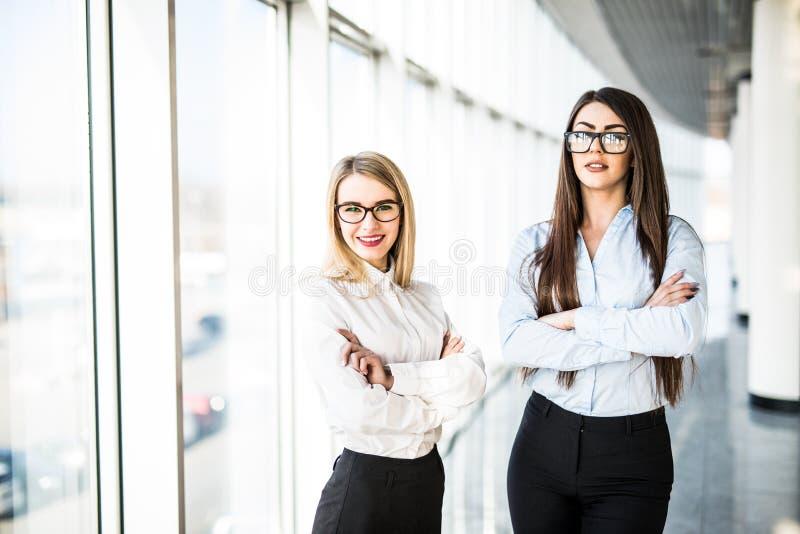 Молодые дамы дела в зале офиса над панорамными окнами стоковые изображения rf