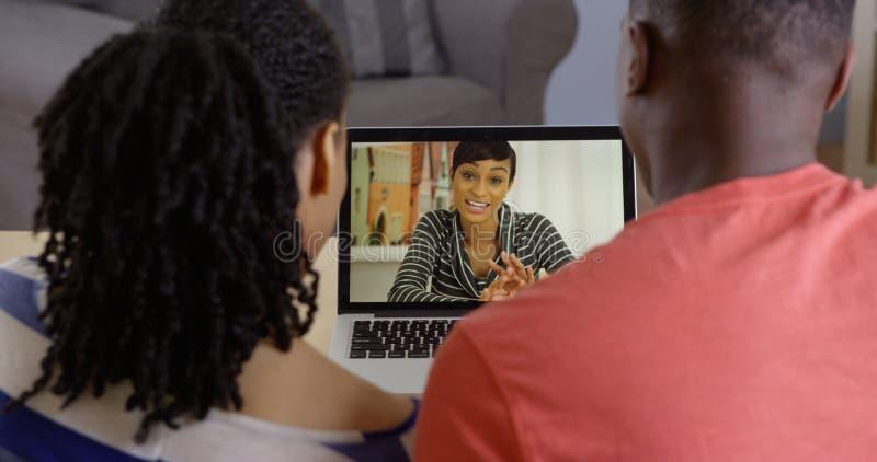 Молодые Афро-американские пары говоря к сестре над болтовней сети стоковые фото
