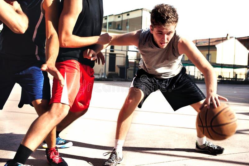 Молодые баскетболисты играя с энергией стоковое фото rf