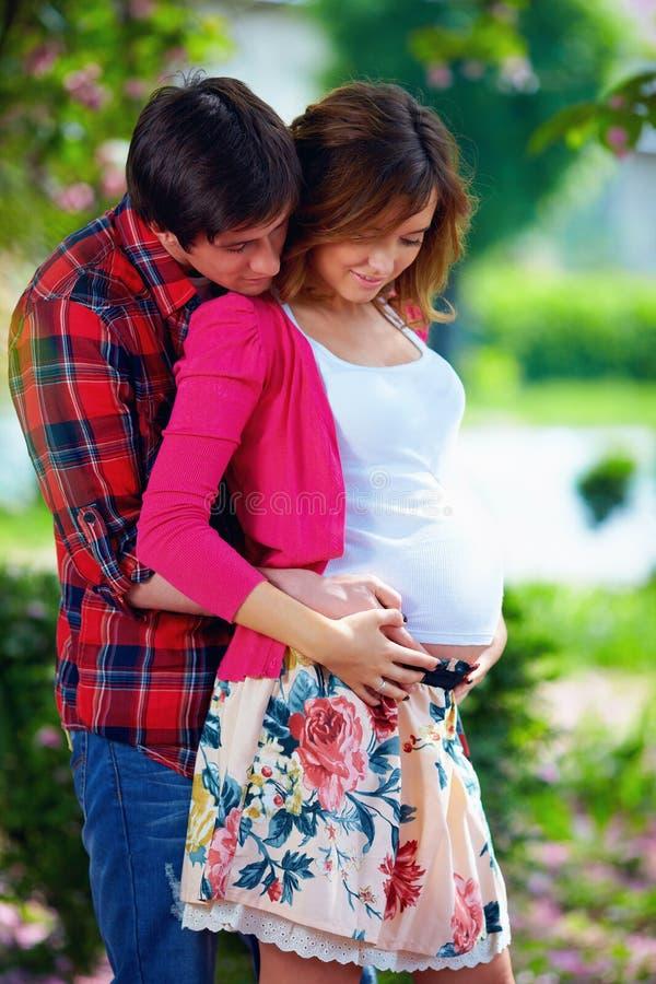 Молодые беременные пары в зацветая парке стоковые изображения