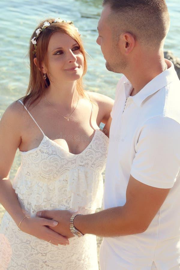 Молодые беременные пары ослабляя на пляже стоковое фото