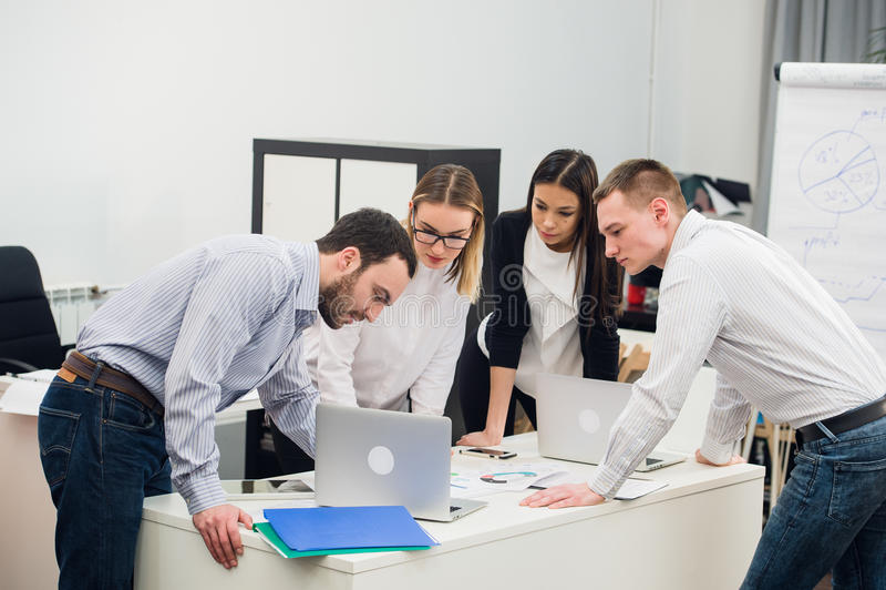 Молодые бизнесмены сидя в офисе во время встречи и обсуждая с обработкой документов используя компьтер-книжки стоковое фото rf