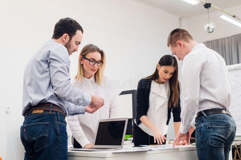 Молодые бизнесмены сидя в офисе во время встречи и обсуждая с обработкой документов используя компьтер-книжки стоковые изображения