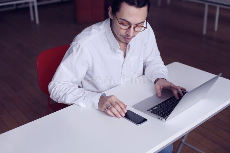 Молодые бизнесмен или студент университета сидя около белой таблицы, работая на компьтер-книжке и используя мобильный телефон в б стоковые фотографии rf