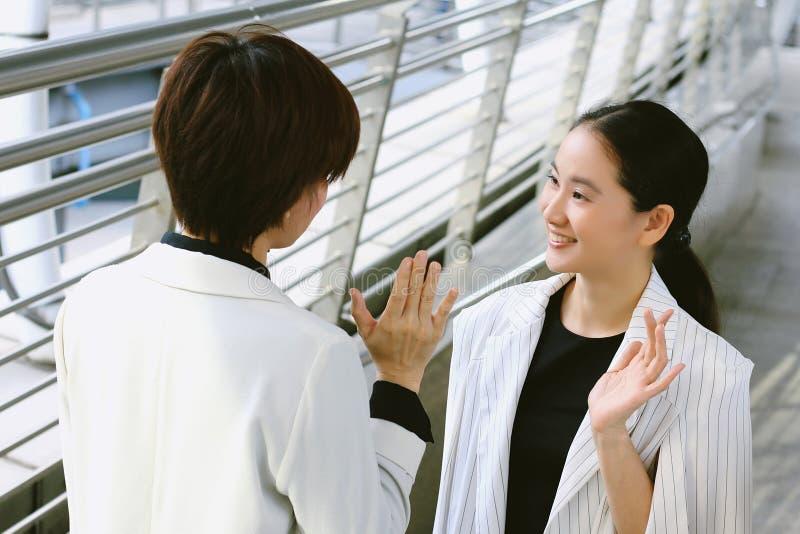 Молодые бизнес-леди приветствуя с усмехаясь стороной, встречей деловых переговоров стоковое фото rf