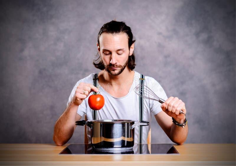 Молодые бородатый человек с варить бак, eggwhish и томат стоковые фото