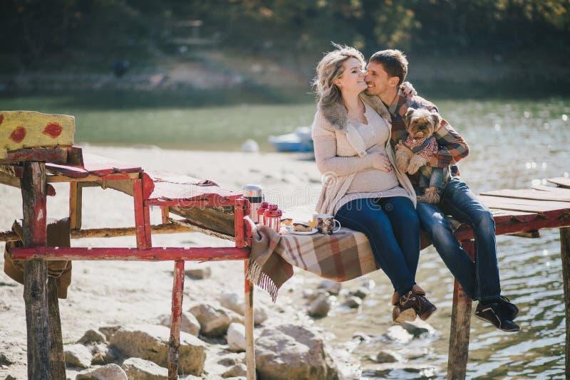Молодые будущие родители и их собака в смешном костюме сидя на деревянном мосте и имея пикник около озера стоковая фотография rf