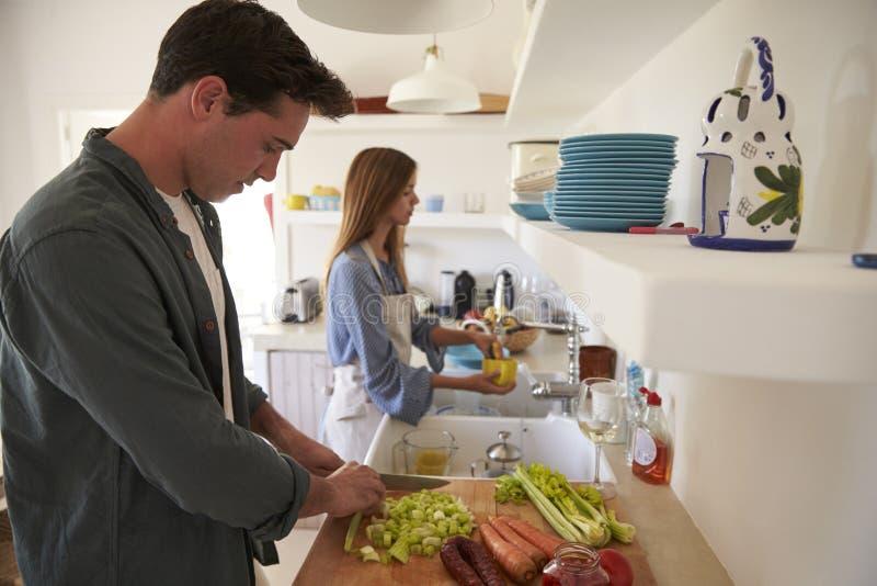 Молодые взрослые пары подготавливая еду, смотря вниз стоковые изображения